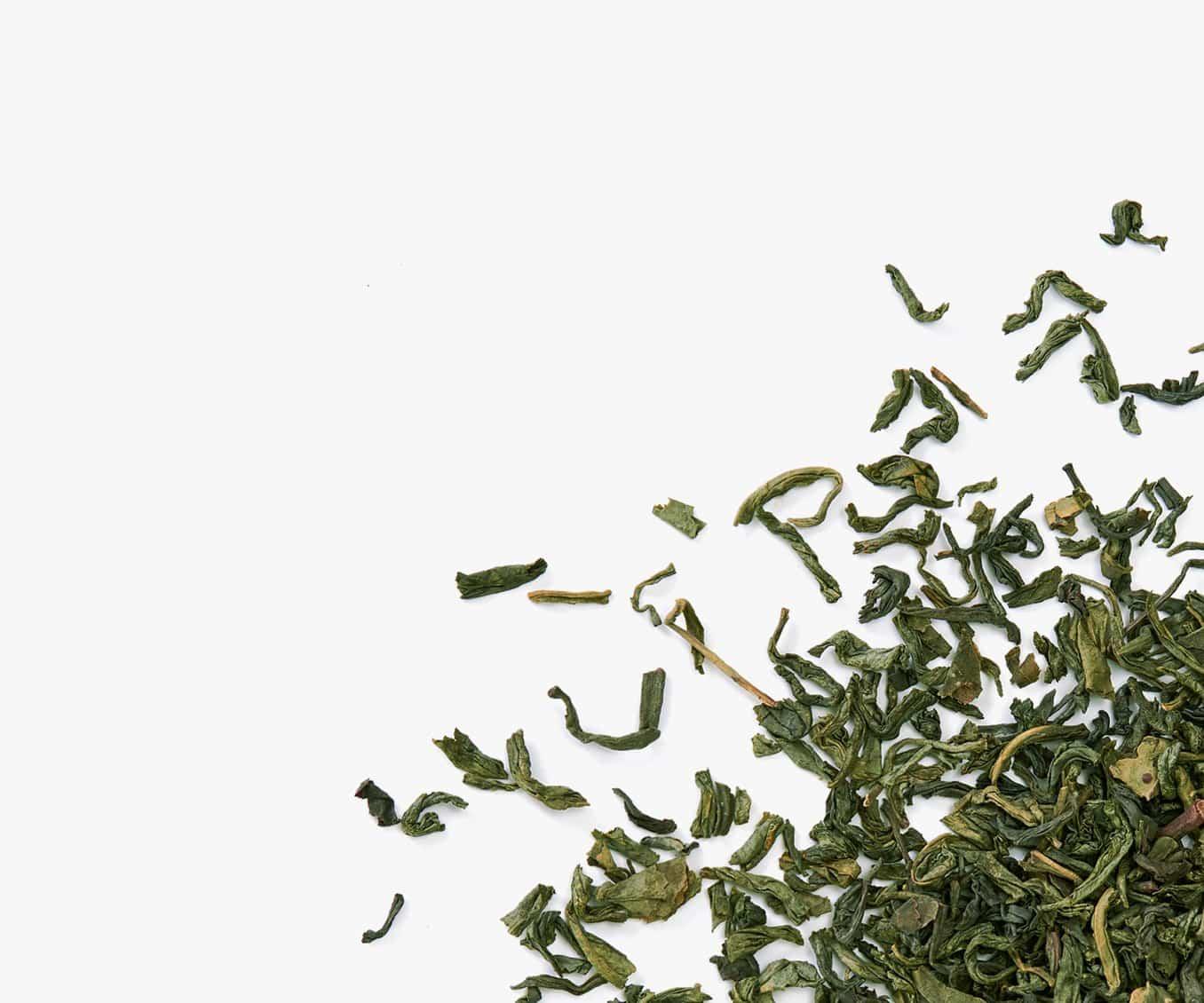 Thé vert en feuille placé dans le coin droit sur un fond blanc.