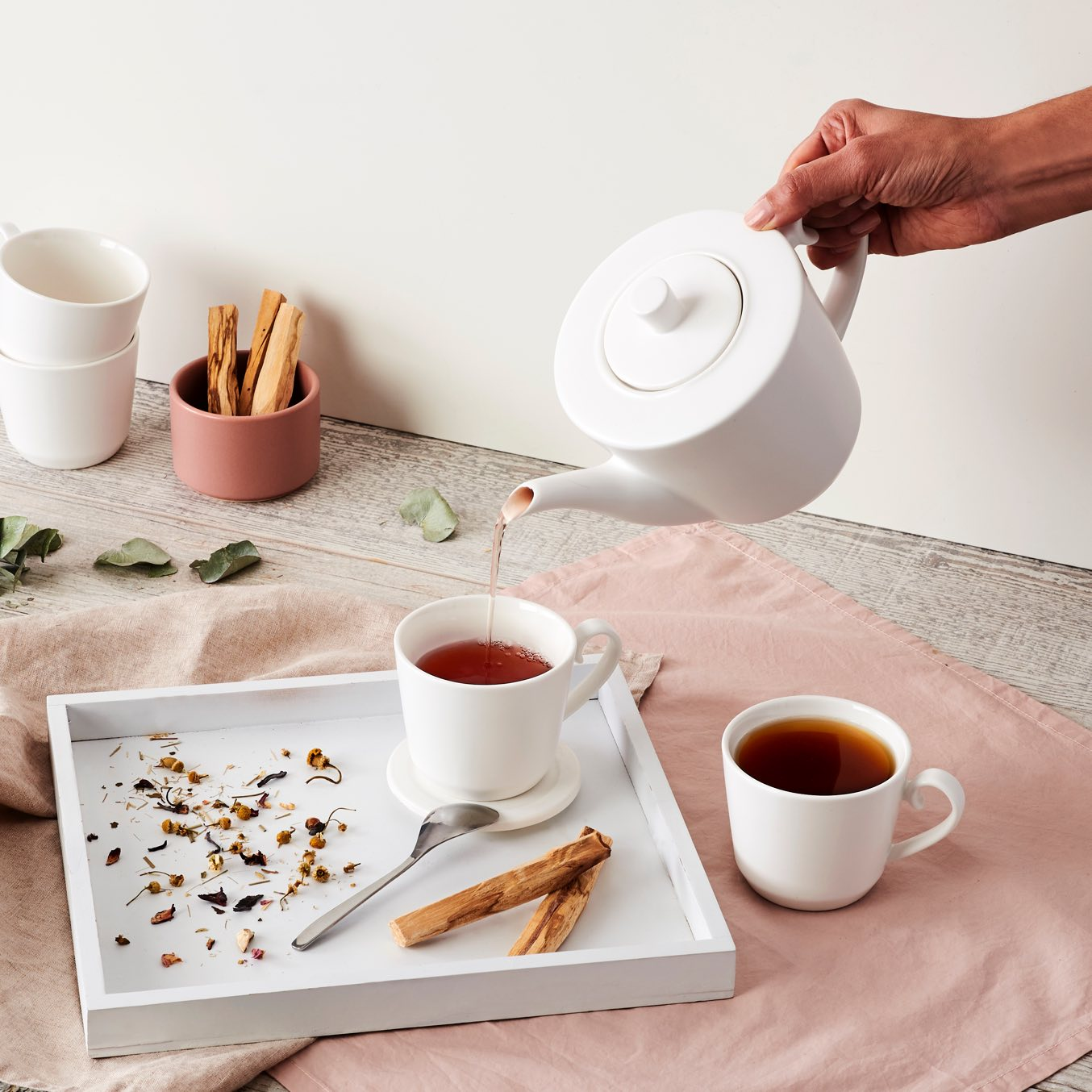Hand pouring hot tea from white 28 oz ceramic teapot into two matching white 7 oz ceramic teacups.
