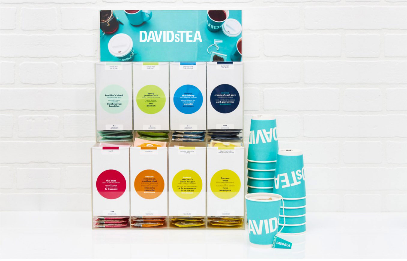 Colourful acrylic tea display with eight types of teas in sachets. Stack of teal DAVIDsTEA to-go beverage cups.