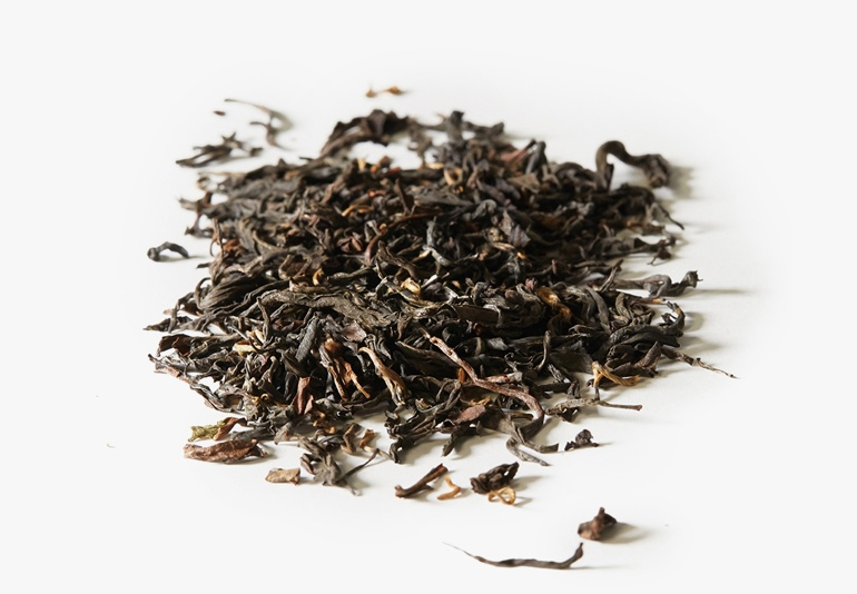Organic Nepal Black tea ingredients placed on a white surface.