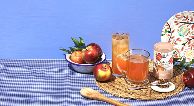 A mug and a glass filled with Apple Cider tea next to fresh apples.