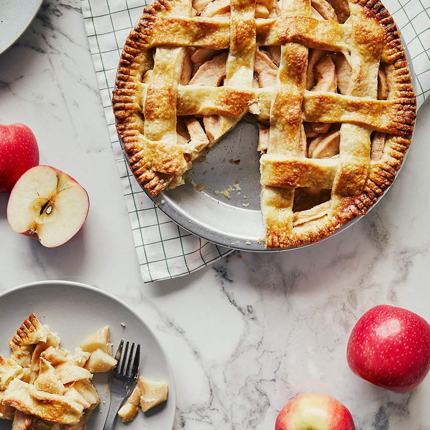 Full classic apple pie with slice missing, plus apple pie slice with lattice top on white ceramic plate with fork.