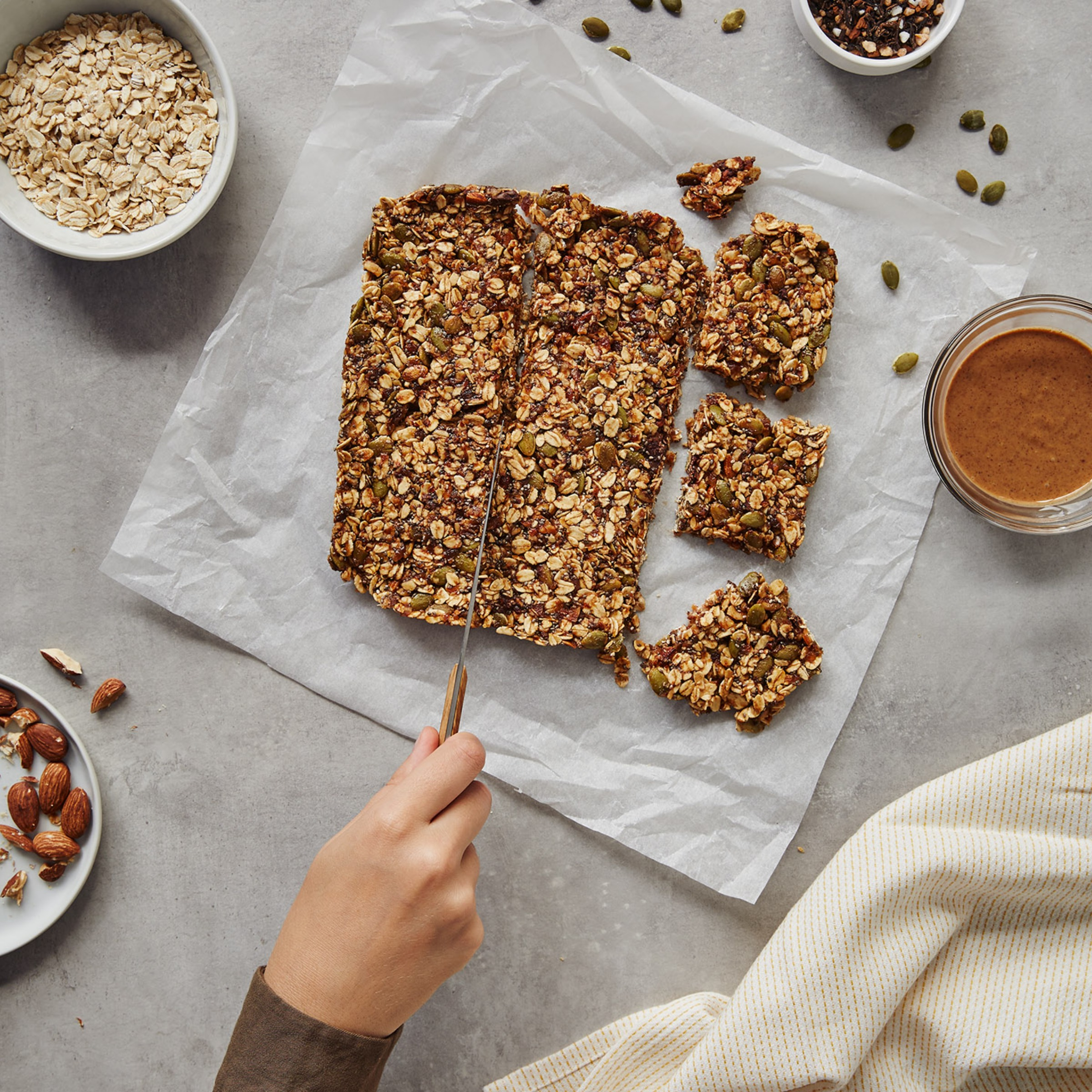 A hand cutting an energy bar in small squares on a kitchen counter