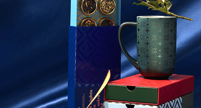 8 tea sampler boxes stacked. A Nordic Mug is placed on top of the three 8 tea sampler boxes with a perfect spoon.