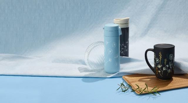 Dandelion Black Colour Changing Nordic Mug and Dandelion Lock Top Travel Mug placed on a sky-blue background.