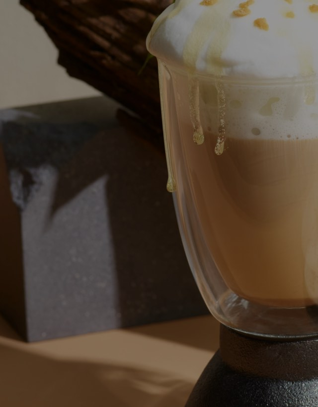 Clear 16 glass mug filled with chai latte topped with frothed milk