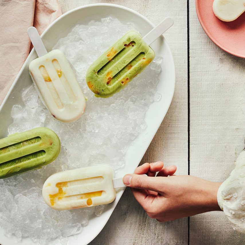 Deux sucettes glacées au yogourt avec poudre de thé vert matcha et tranches de pêche, deux autres avec thé glacé et tranches de pêche.