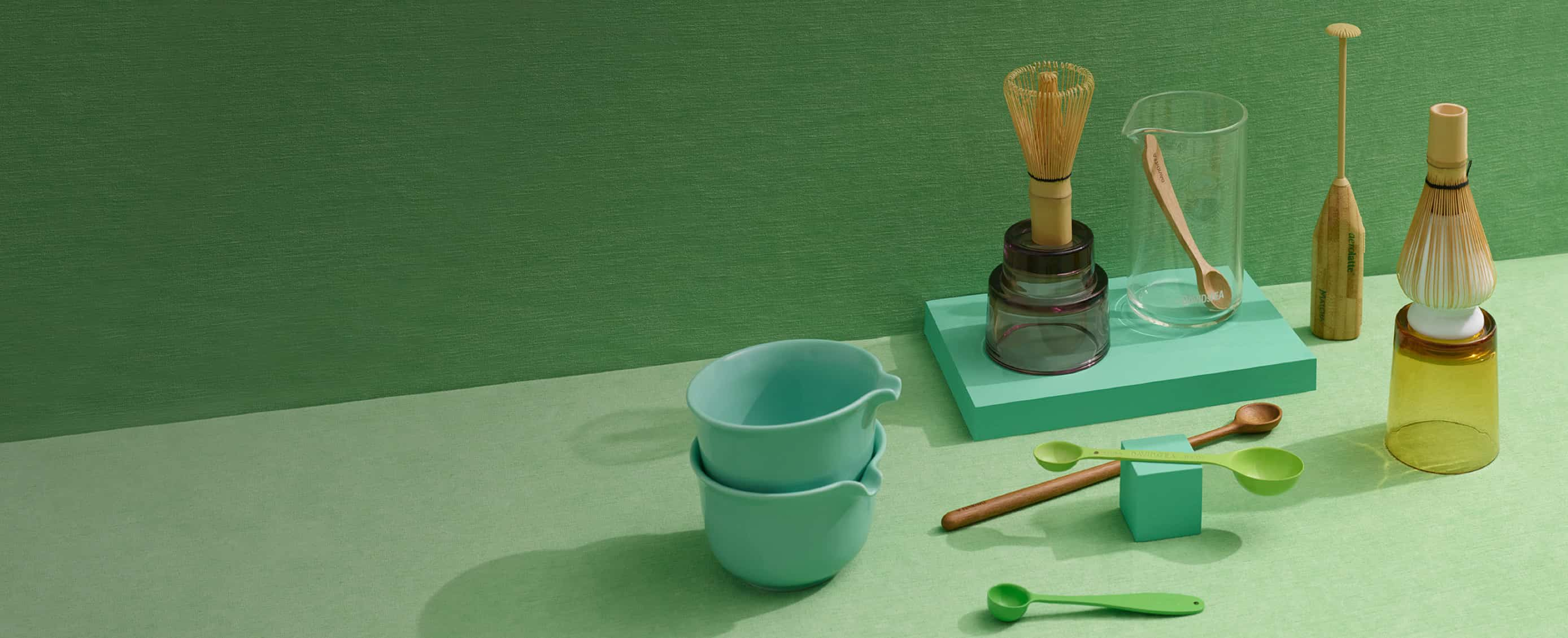 Empty matcha bowl with spout, bamboo matcha whisk on whisk holder, bamboo spoons, clear glass beaker.