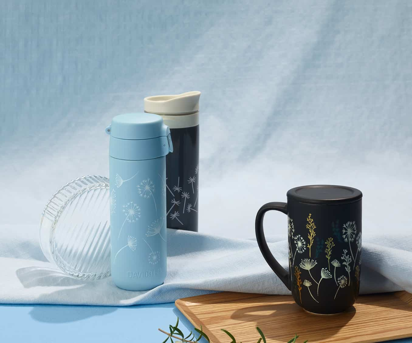 Dandelion Black Colour Changing Nordic Mug and Dandelion Lock Top Travel Mug placed on a sky-blue background.