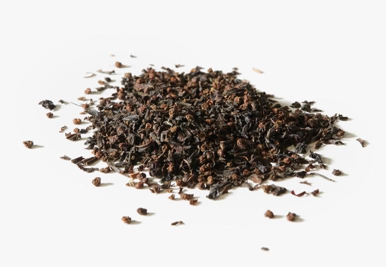 Des ingrédients du thé Mélange Breakfast de David biologique, placés sur une surface blanche.