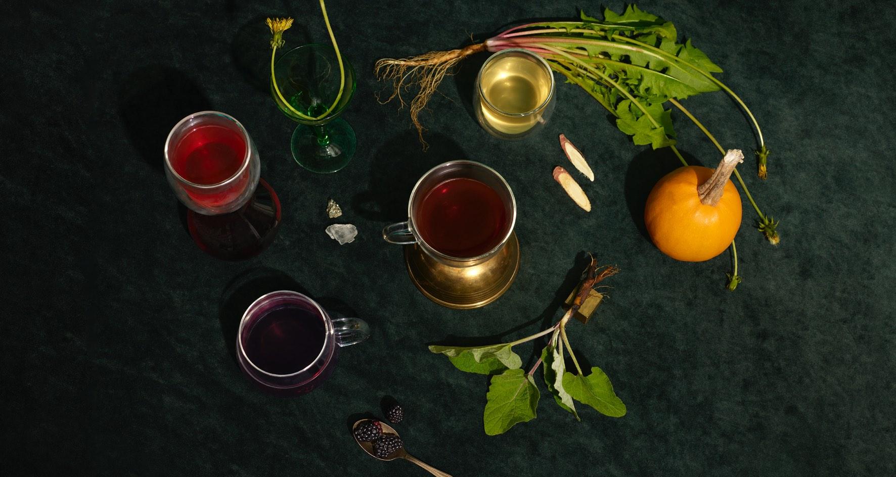 Quatre tasses en verre remplies de thés naturels contenant des ingrédients mieux-être traditionnels: bardane, racine de pissenlit, mûres.