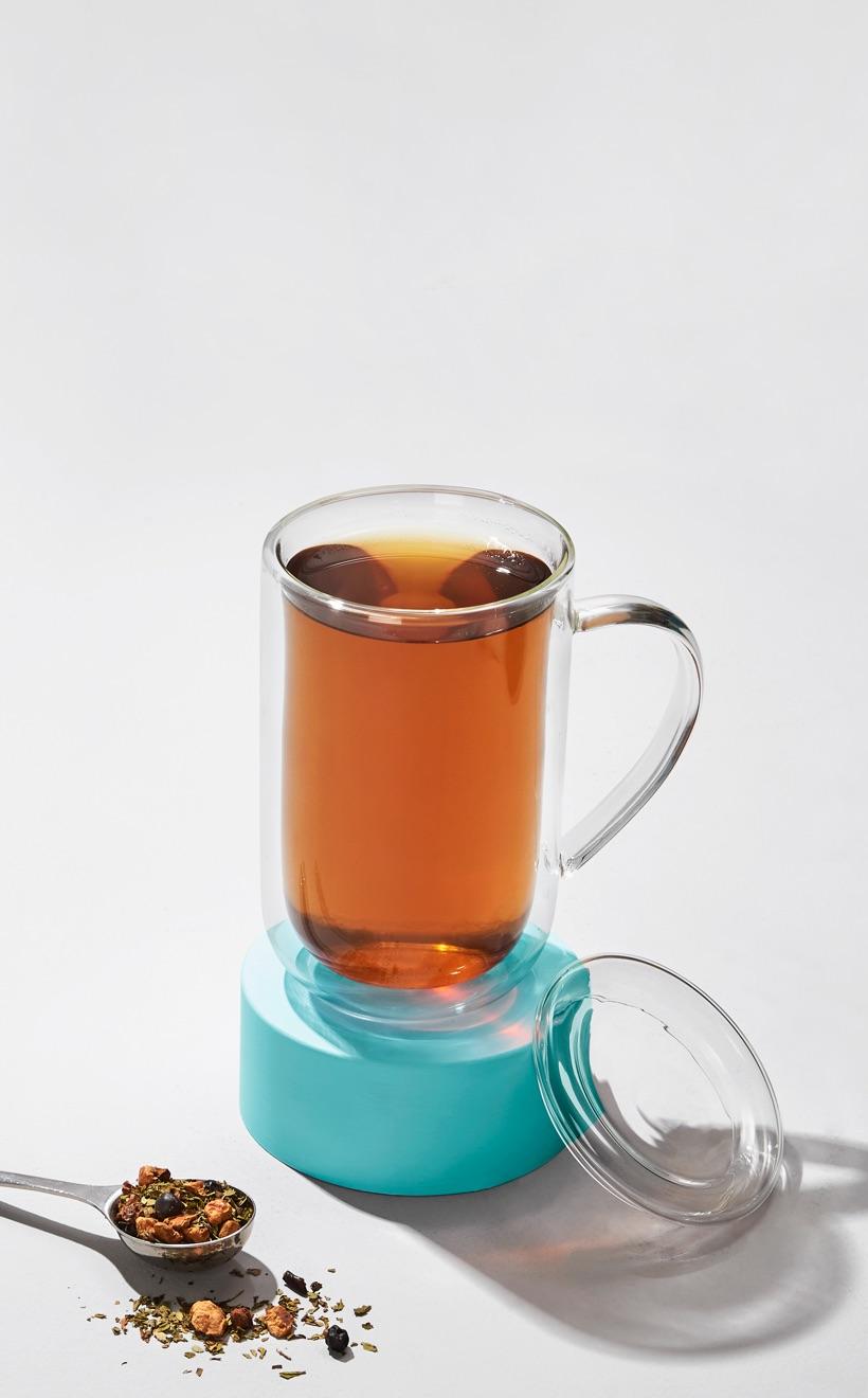 Tasse nordique en verre remplie de thé Cold 911 debout sur une soucoupe turquoise. Cuillère parfaite en argent remplie de thé en feuilles.