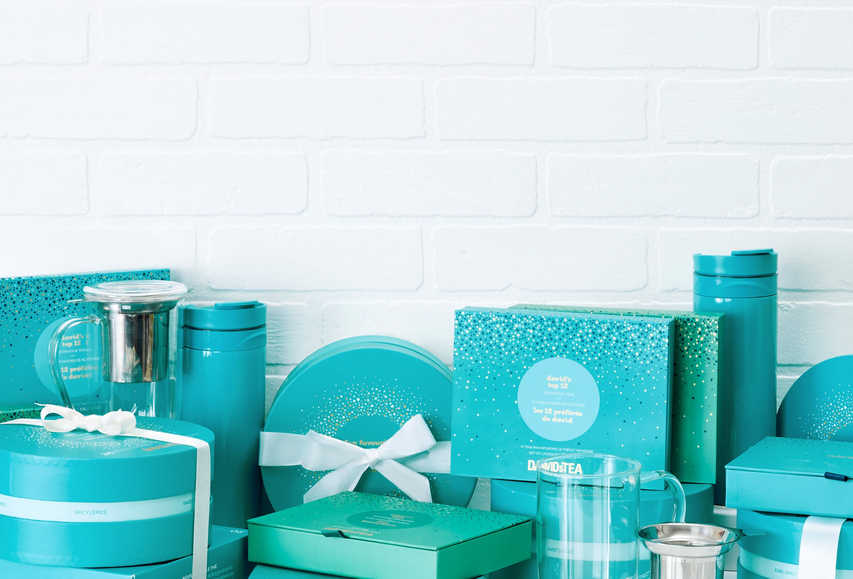 Assortment of teal tea gift sets, ready-to-gift tea samplers, clear 16 oz mugs with tea infusers, 16 oz teal travel mugs.