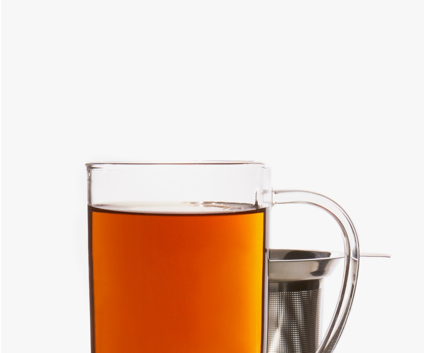 Clear 16 oz glass mug filled with chai in front of stainless steel tea infuser.