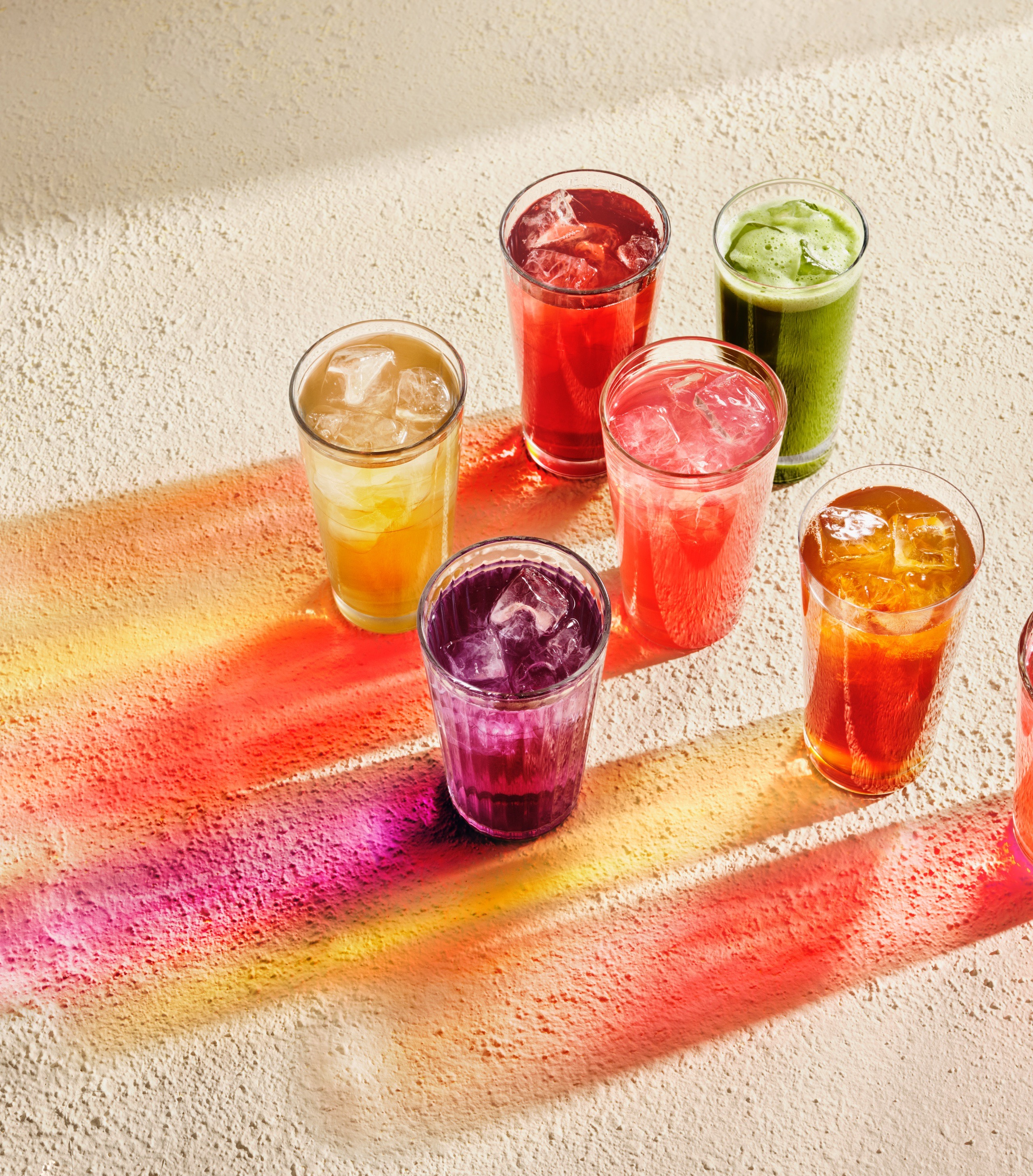 Sept verres remplis de thés glacés laissant percevoir leurs ombres colorées.