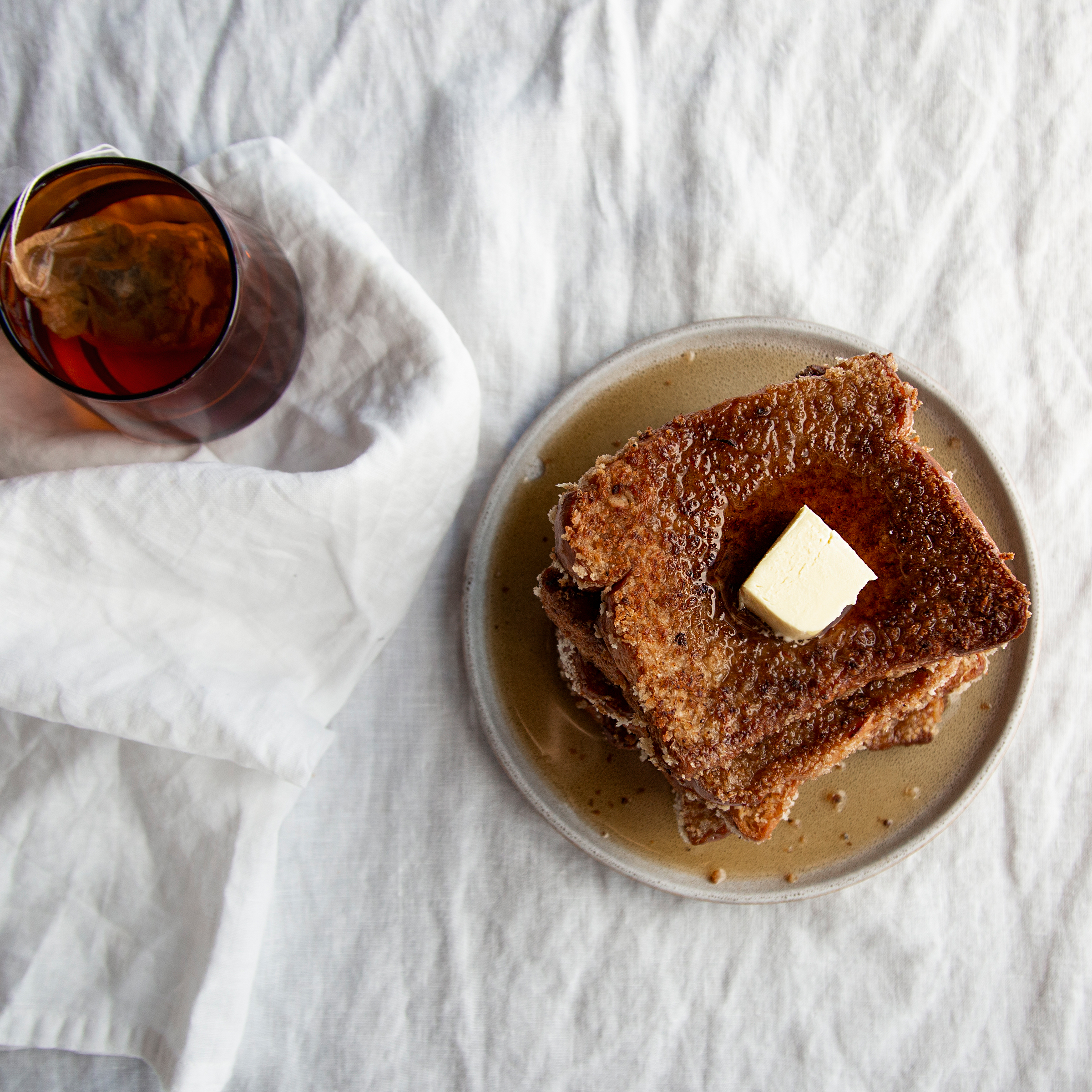 French toast on a brown plate placed on a white cloth.