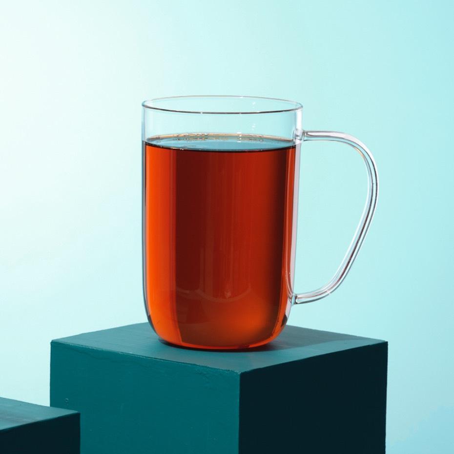 Une tasse transparente remplie du thé Earl Grey crème biologique des thés DAVIDsTEA.