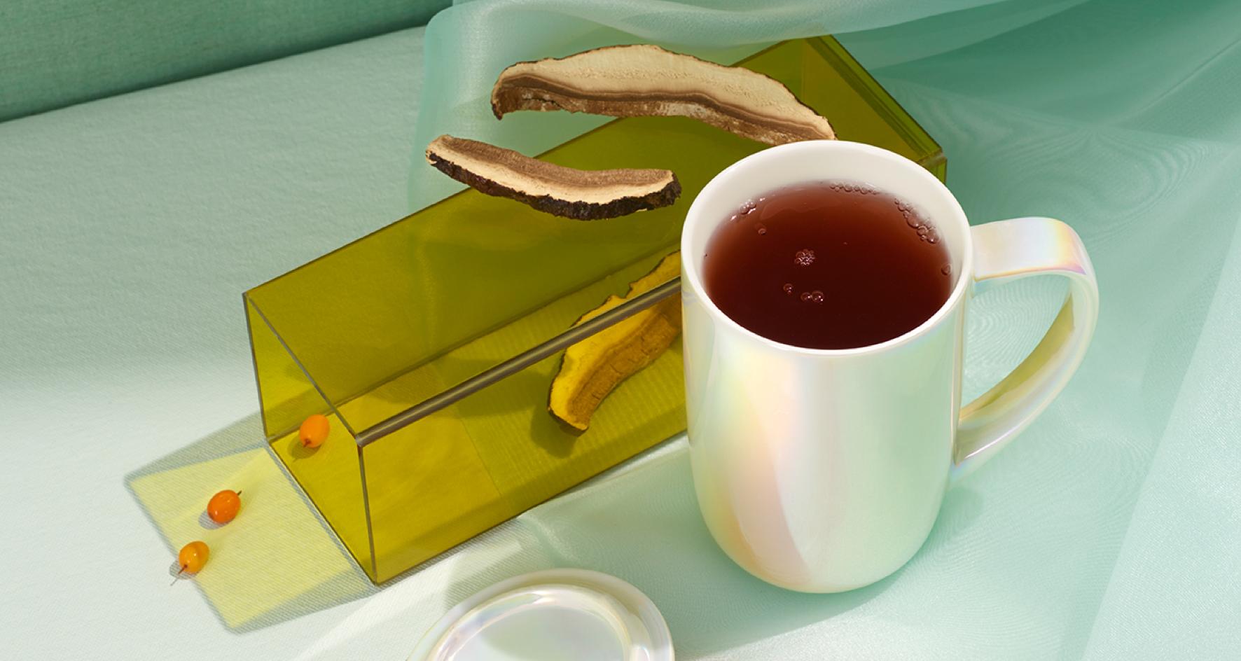 Tasse Nordic remplie de thé Reishi détente placée à côté des ingrédients crus.