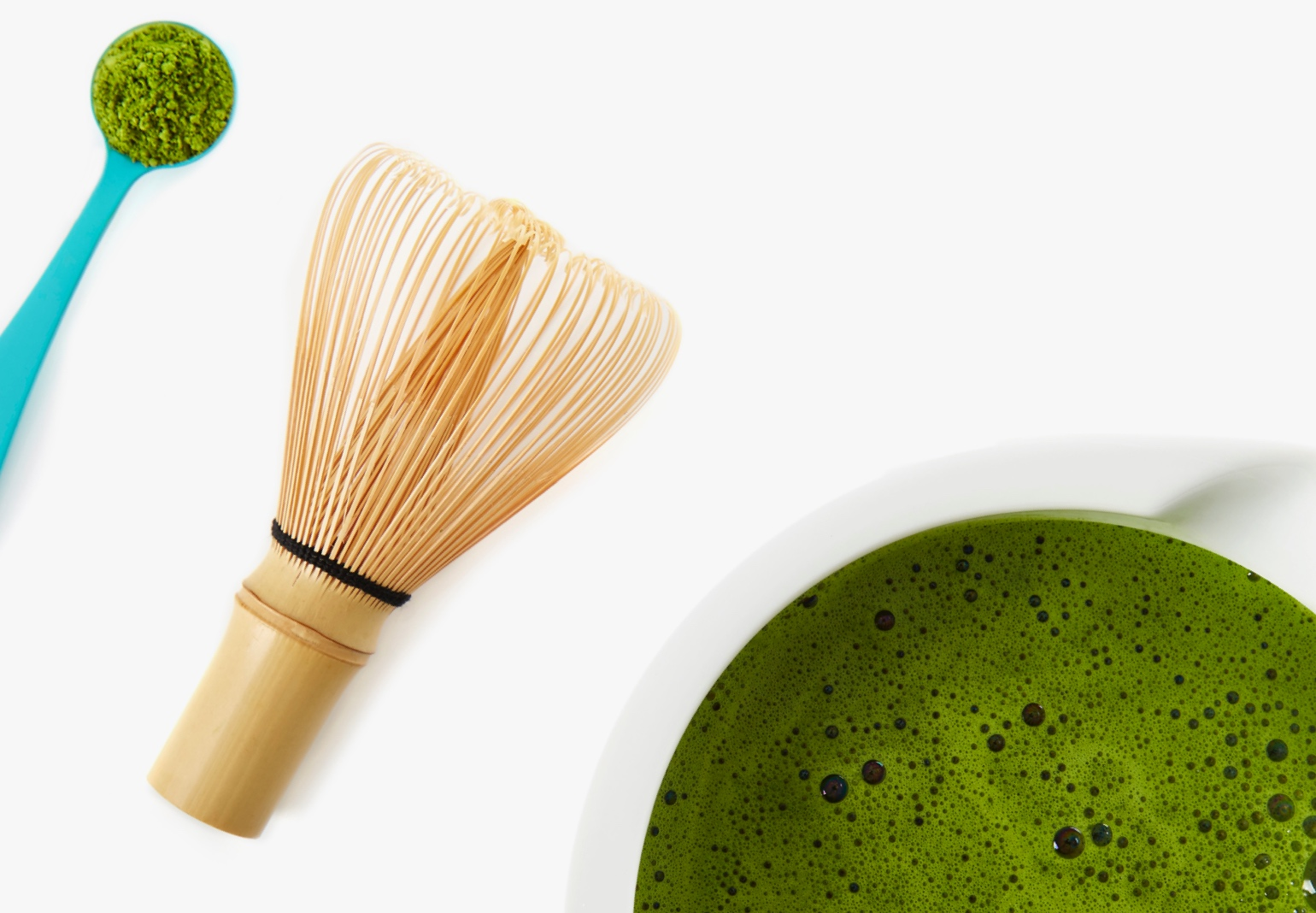 A whisk, spoon and bowl filled with matcha.