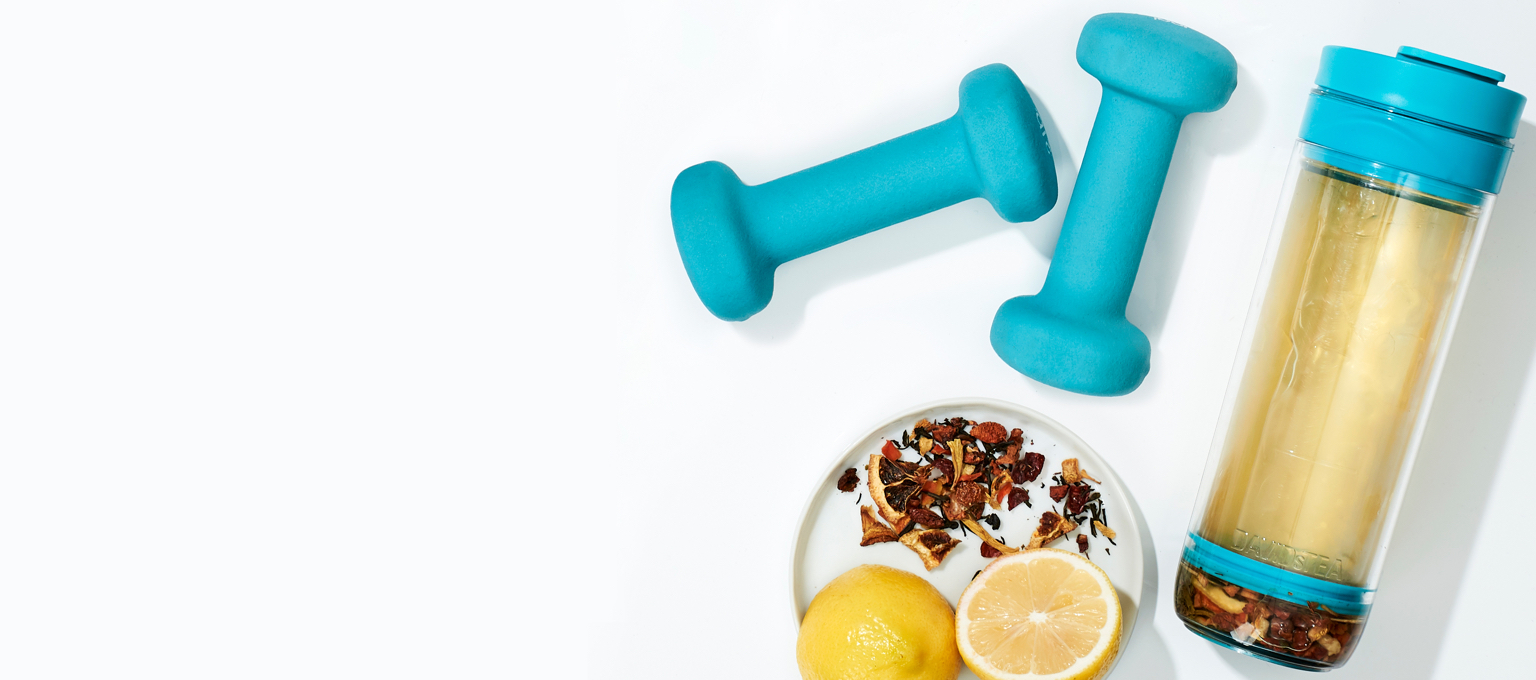 Exercise equipment next to a tea press and raw ingredients and a sliced lemon.