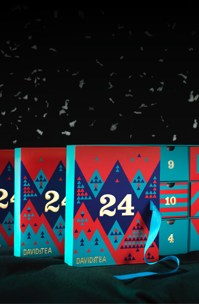 Artificial snow falling on three 24 Days of Tea book boxes set on a black background.