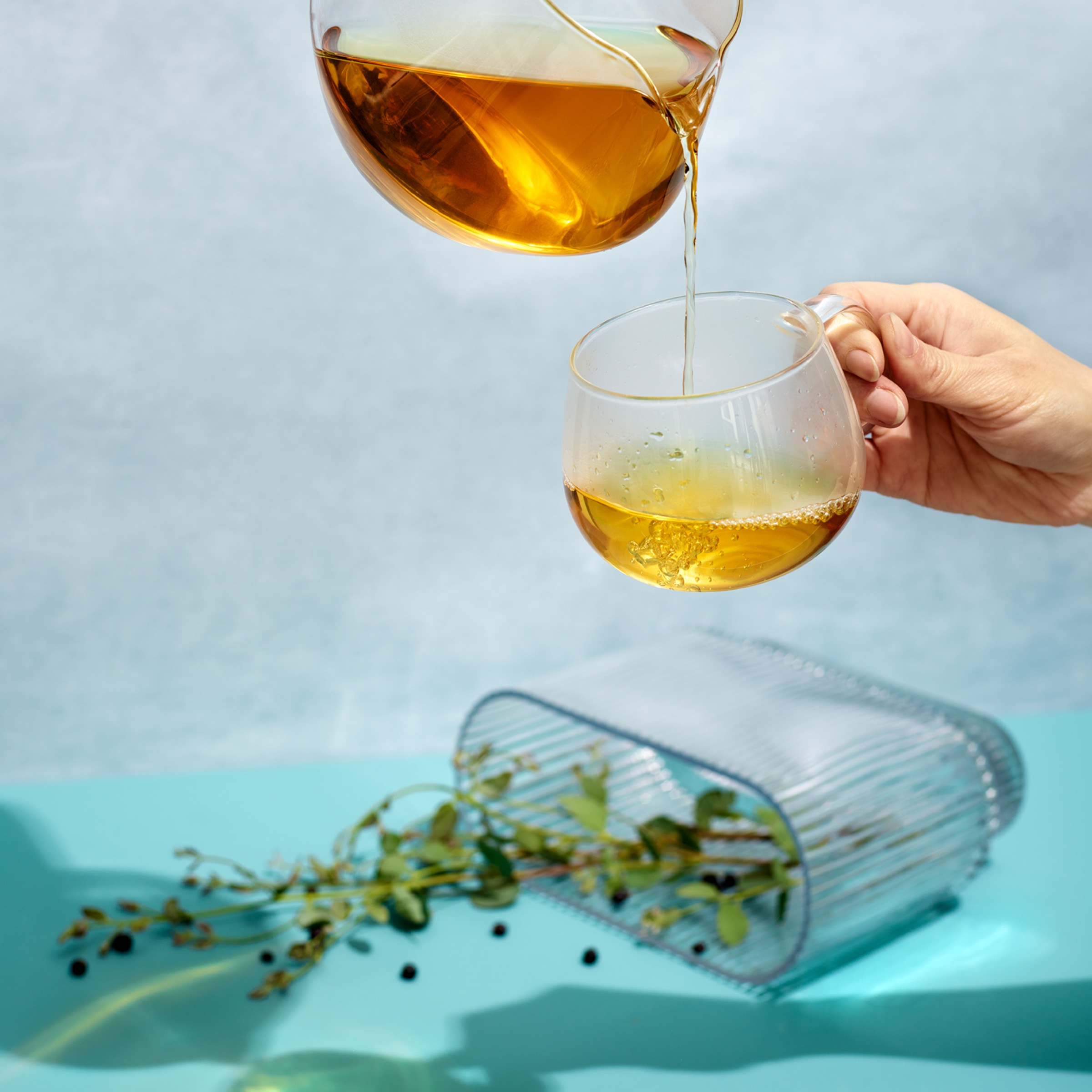 Tea being poured in a glass cup above a plant vase tipped on its side.