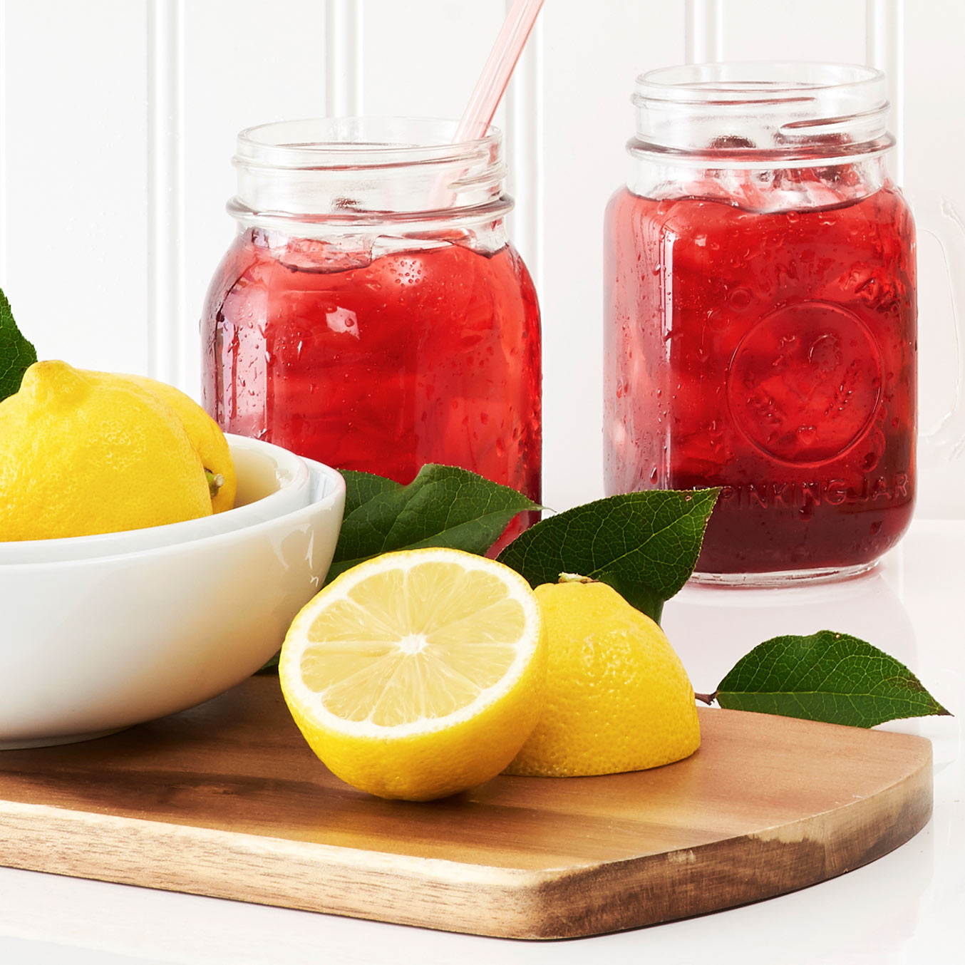 Two glass jars filled with iced tea next to a sliced lemon.
