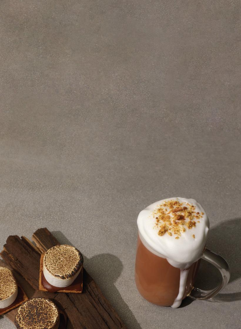 Tasse en verre remplie de thé chaï avec lait moussé. Accompagné d'un dessert s'mores.