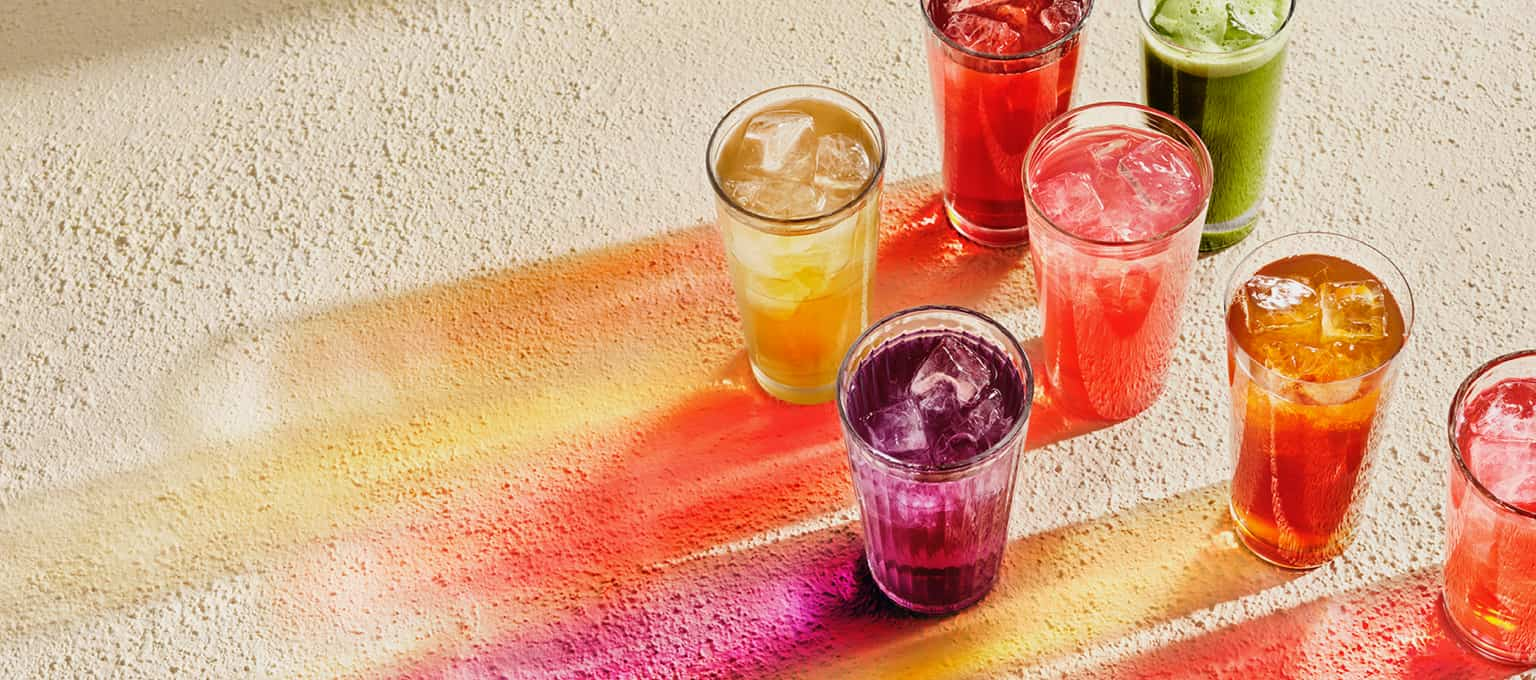 7 steeped iced teas in clear glasses representing a rainbow with their different colors.