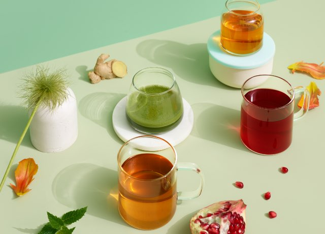 Four glasses filled with DAVIDsTEA new wellness teas: Peachy Clean, Echinacea Shield, Organic Bed of Roses, and Dandelion Detox.