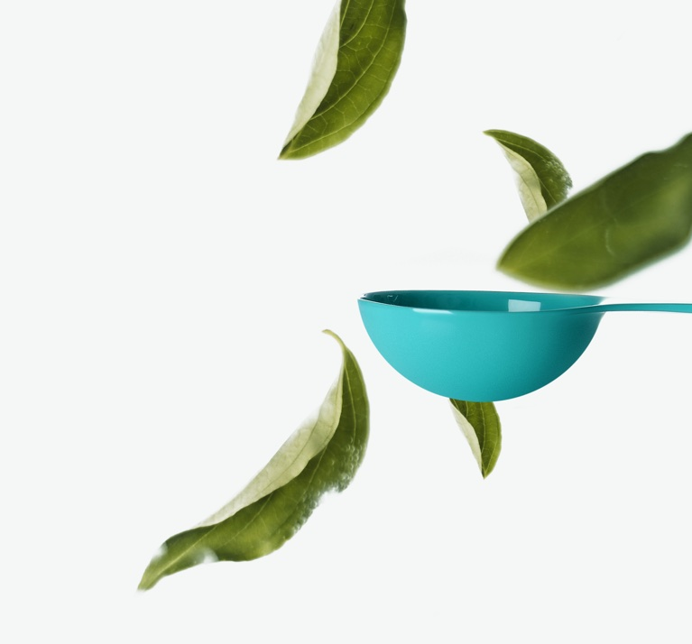A teal Perfect Spoon with falling tea leaves.