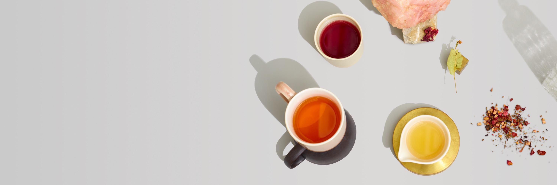 3 tasses de céramique remplies de thés mieux-être chauds contenant des ingrédients favorisant l'équilibre naturel.