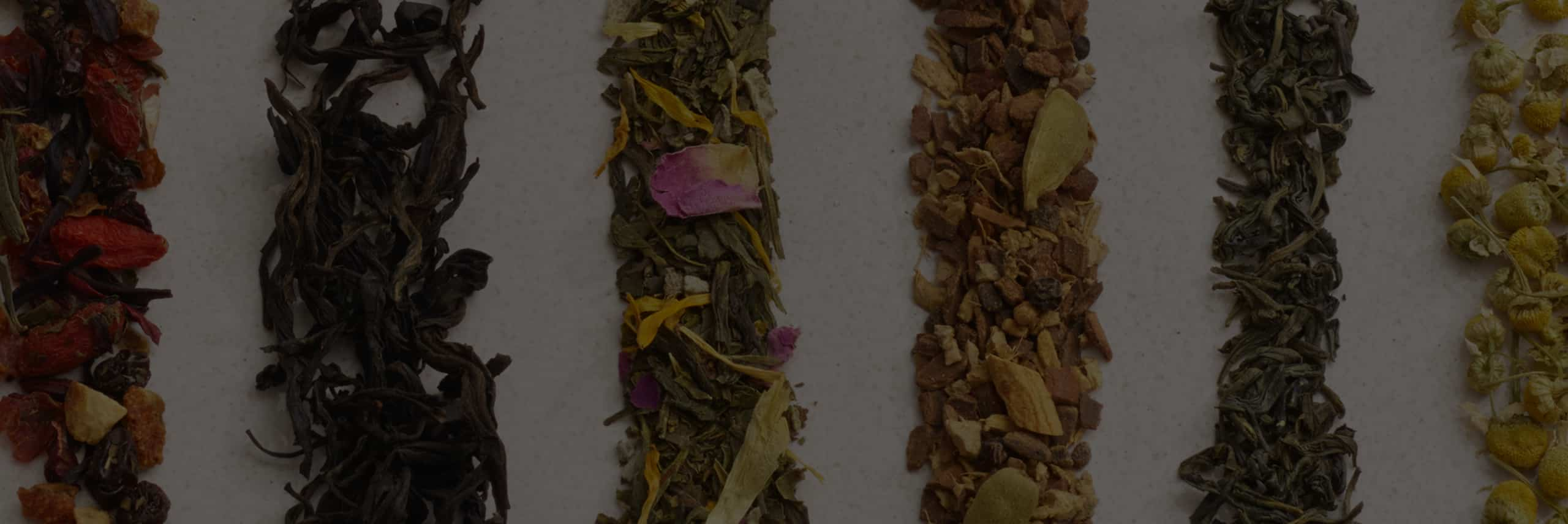 Six colourful loose leaf teas beautifully displayed in vertical lines.