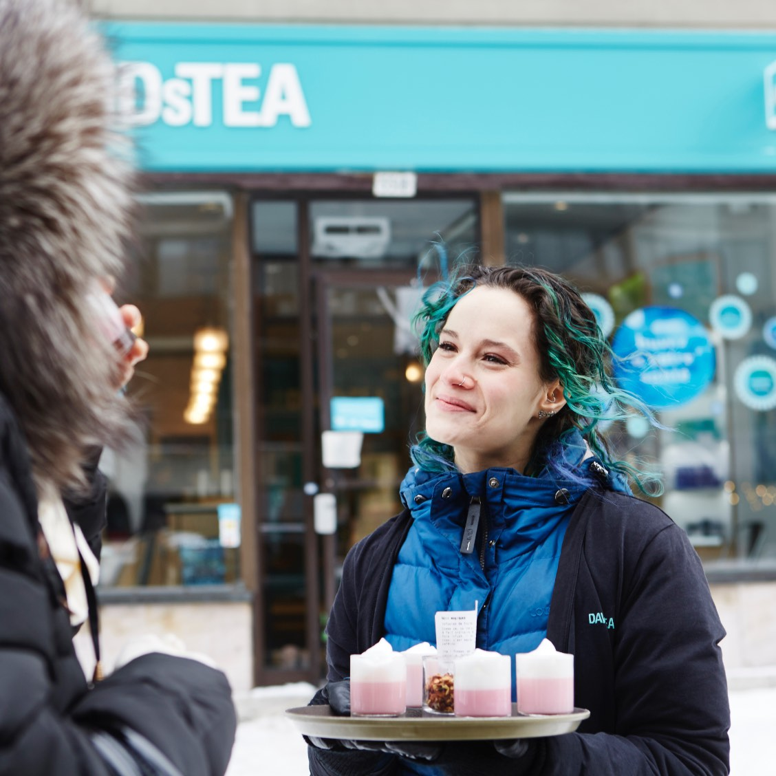 An employee holds a tray of tea latte samples outside a DAVIDsTEA store, she's smiling ear to ear.