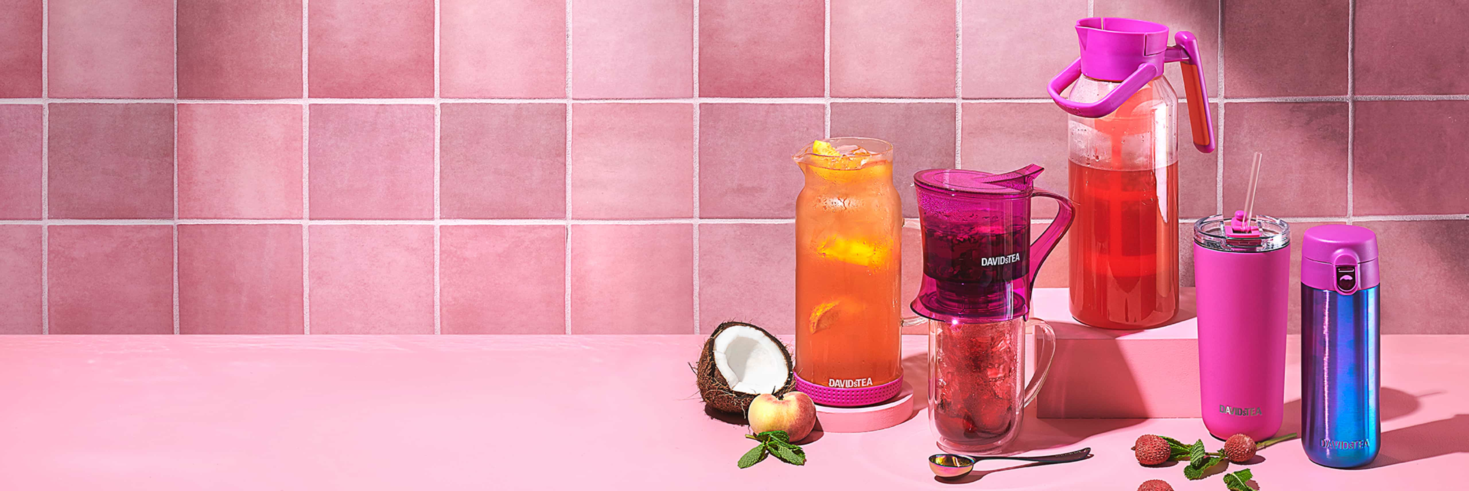 Multiple tea-serving accessoires filled with iced teas next to raw fruits & accessories.
