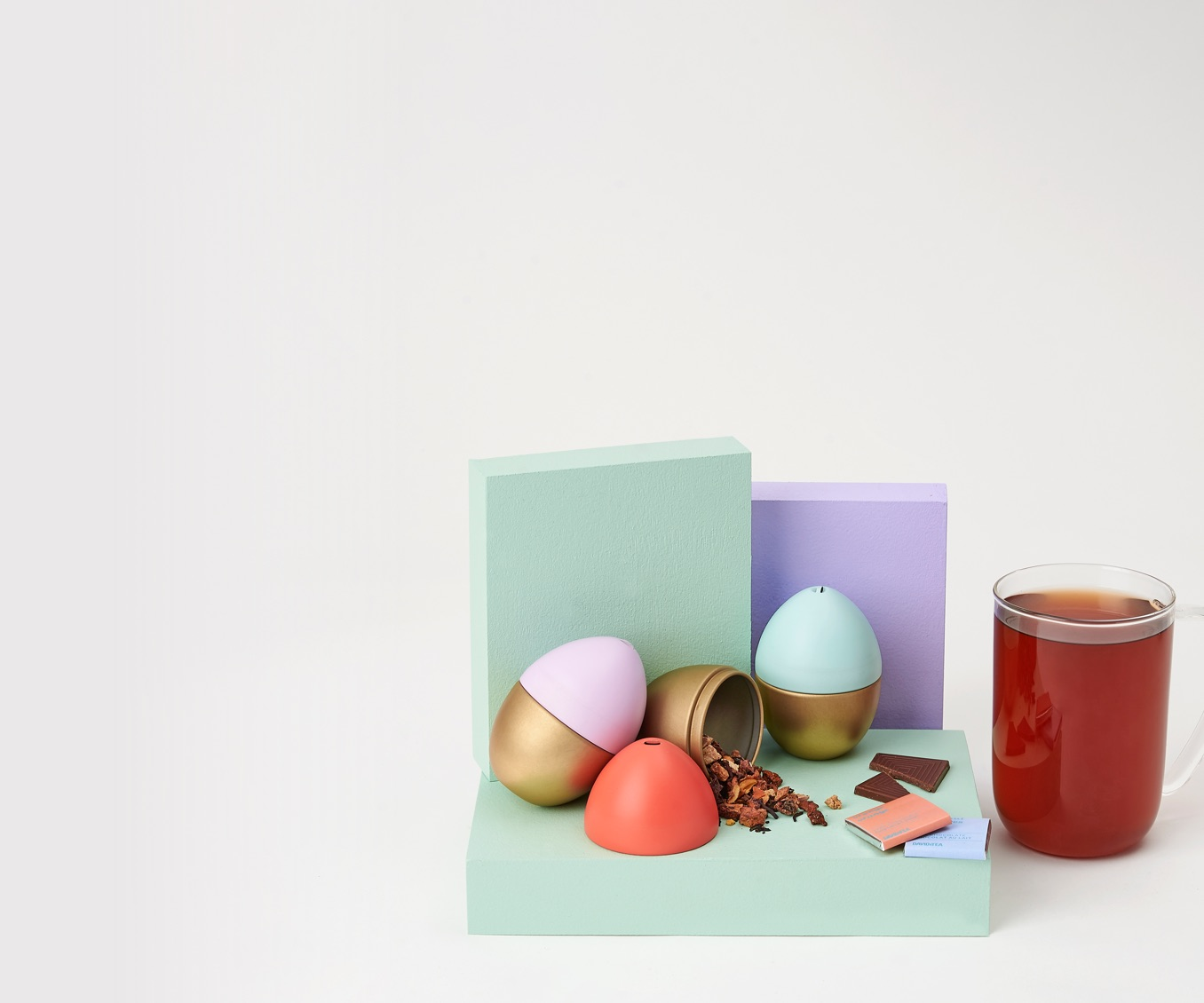 Three Easter egg tins filled with sweet loose leaf teas. Clear 16 oz glass mug filled with tea.