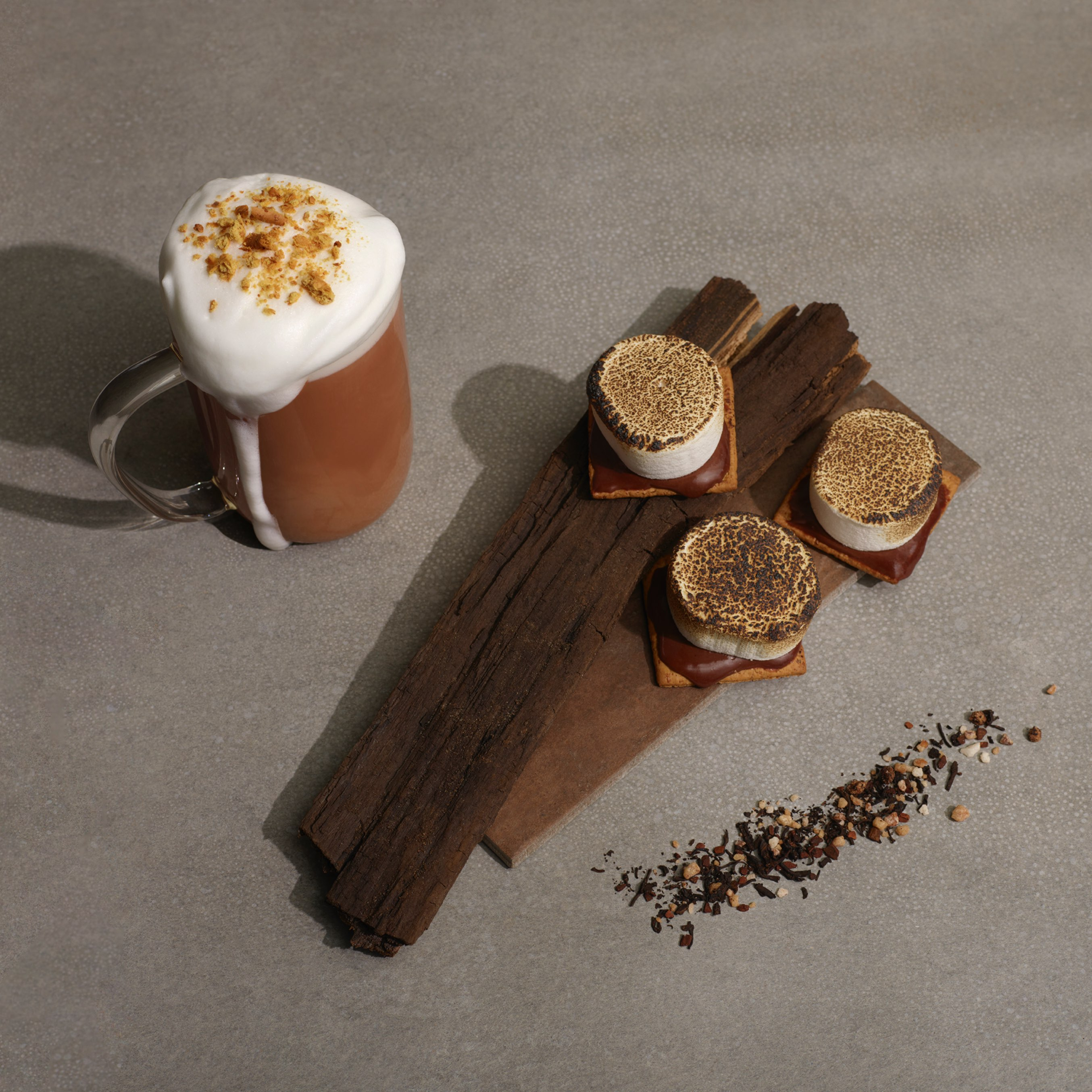 Clear 16 oz glass mug with S'mores Chai pu'erh tea accompanied by s'mores dessert on logs.