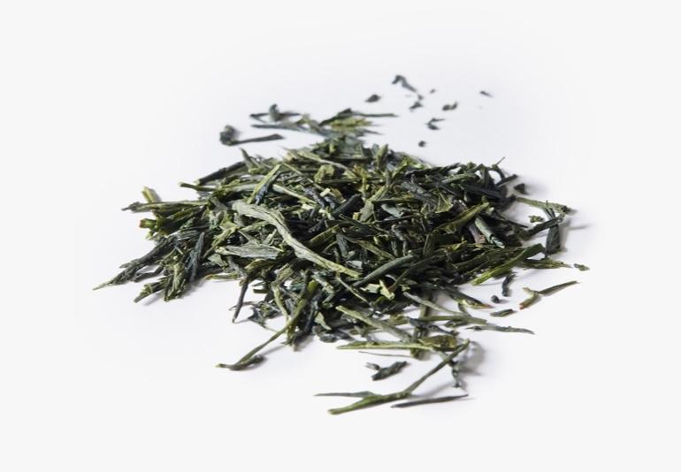 Des ingrédients du thé Sencha du Japon biologique, placés sur une surface blanche.