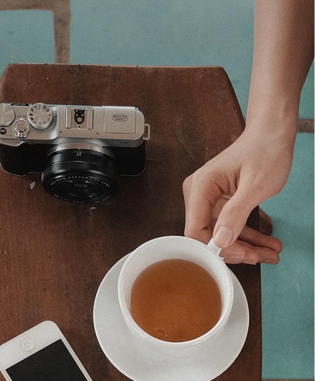 Une image vue de haut d'un iPhone blanc, tasse et caméra noire placés sur une table de bois sur une surface de tuiles turquoises.