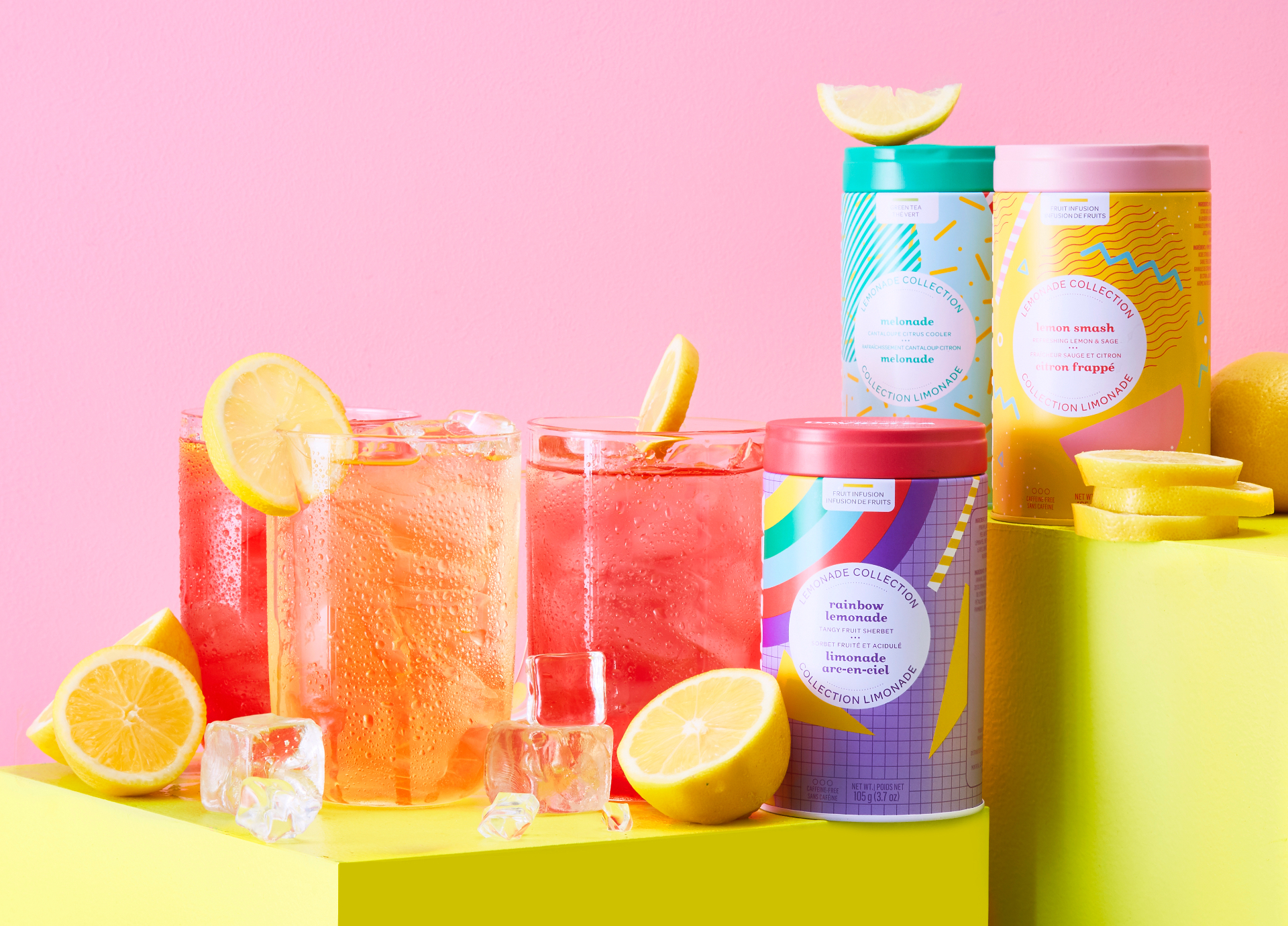 Three clear 16 oz glass mugs with lemonade iced tea and lemon slices, plus three colourful loose leaf tea tins.