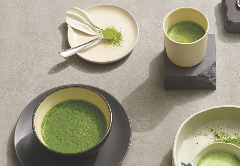 Various matcha-filled cups and bowls next to each other.