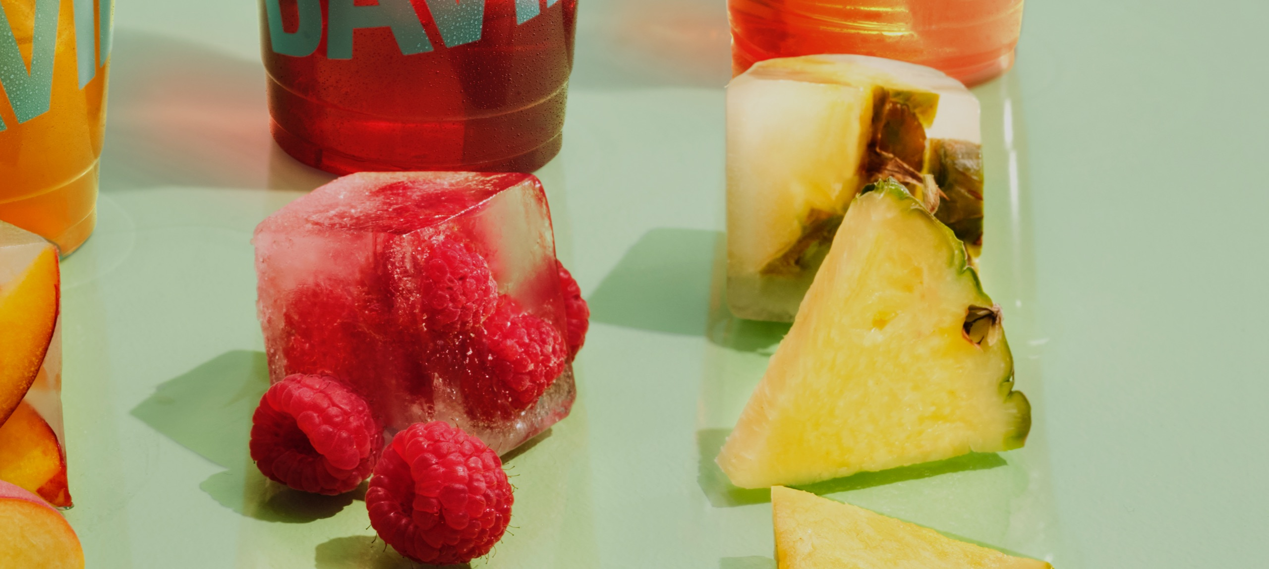 Three cups filled with iced teas with peach, raspberries and pineapples placed in front.