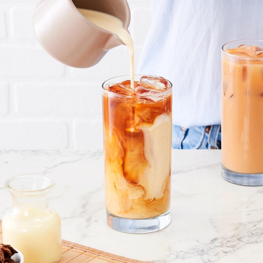 Lait versé dans un grand verre transparent avec du thé glacé thaï.