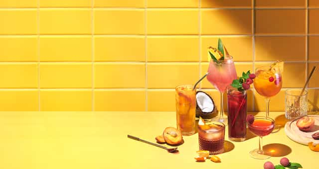 Multiple glasses filled with iced teas next to raw fruits & accessories.
