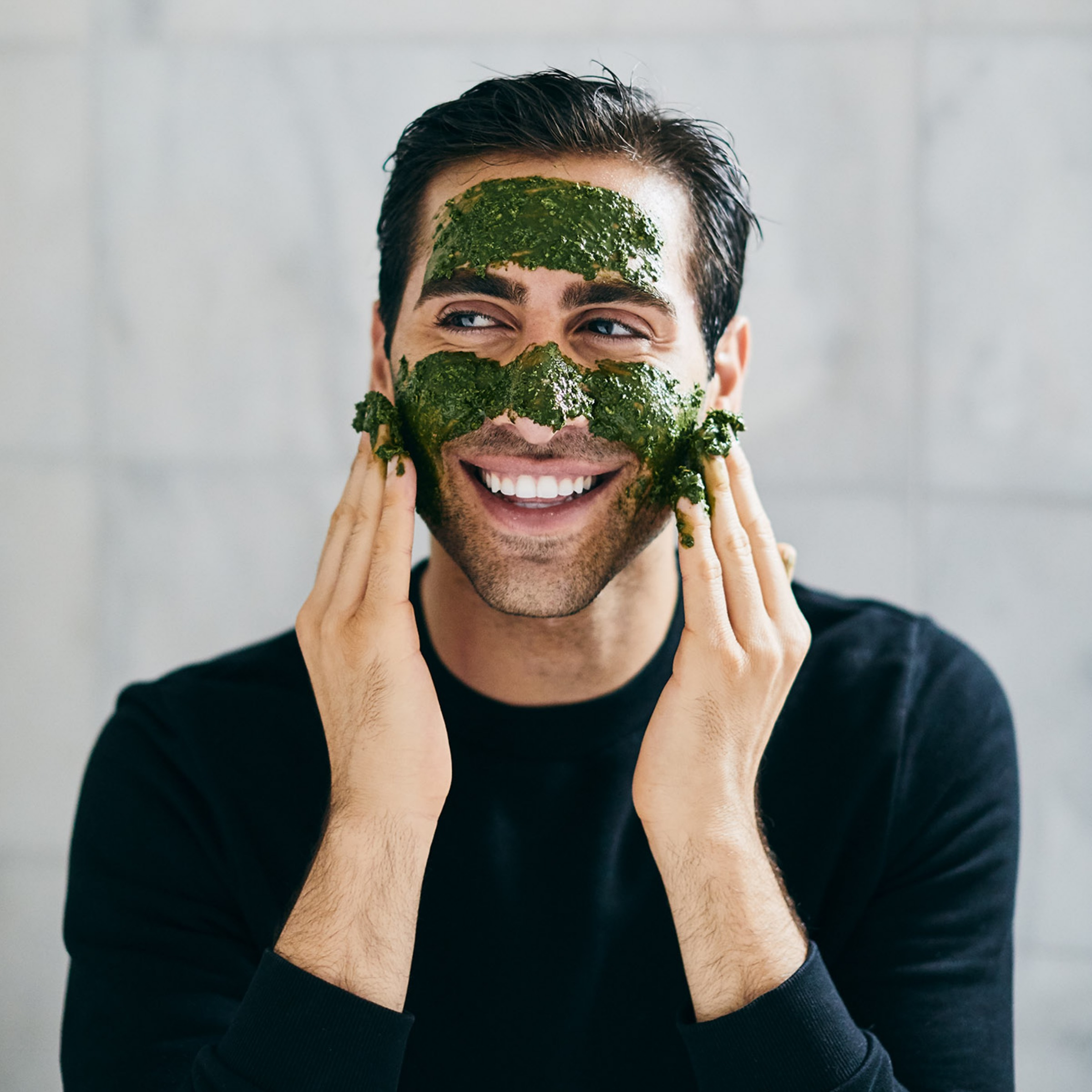 A person smiling while applying the matcha face mask in a bathroom