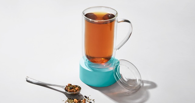 Glass nordic mug filled with Cold 911 tea standing on a teal saucer. Silver perfect spoon filled with loose leaf tea.