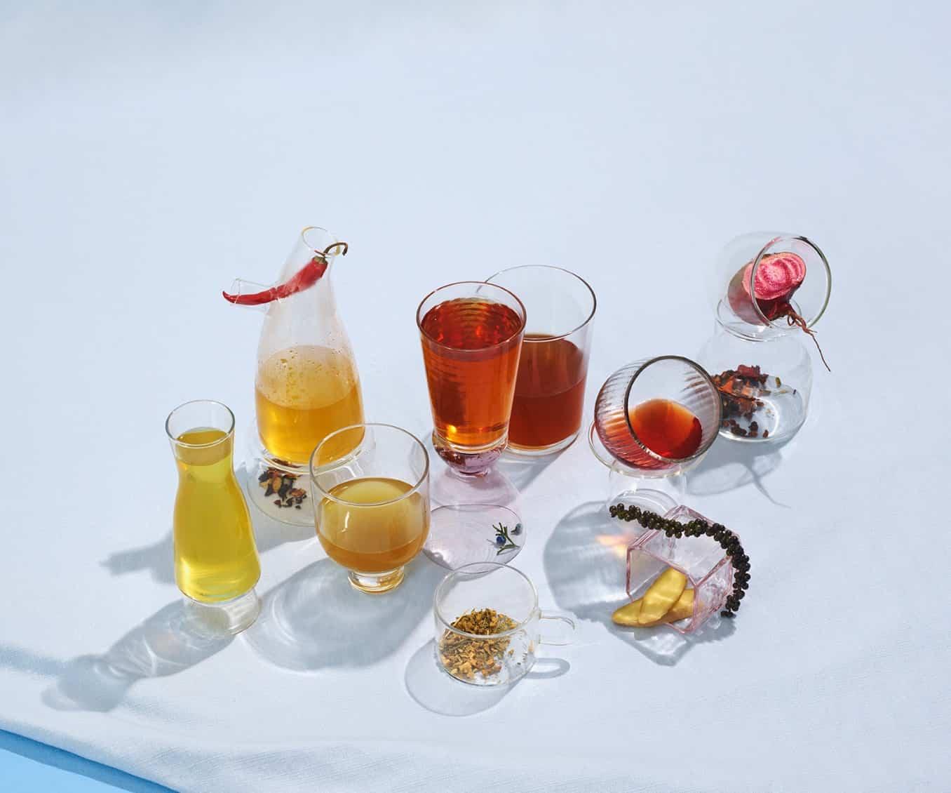Des verres variés remplis de thés détox, entourés par des ingrédients crus tels que des betteraves et des piments.