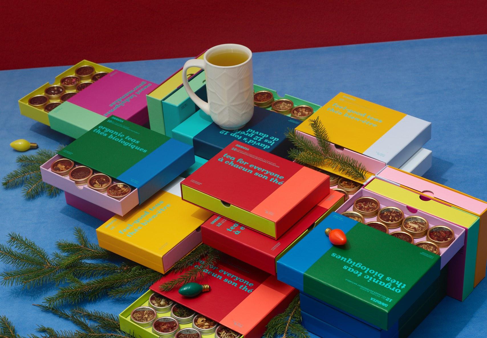 Variété de boîtes de 8 thés empilées à l'horizontale avec des branches de pin et une tasse des fêtes.