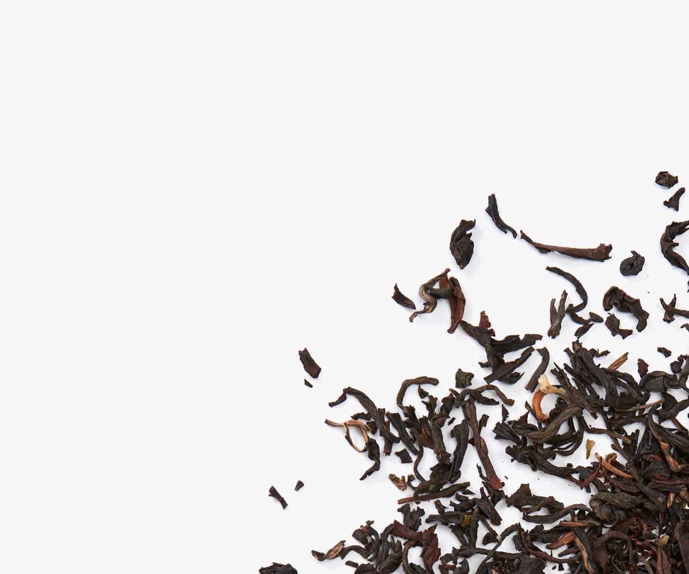 Loose leaf black tea placed in the bottom right corner on a white background.