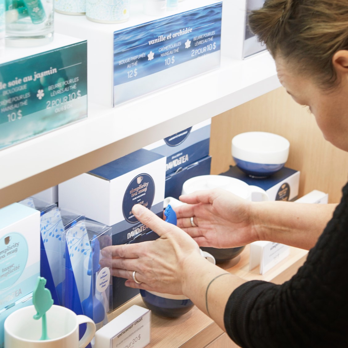 An employee arranges items on a shelf inside a DAVIDsTEA store.